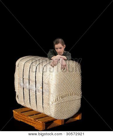 Teenage Woman Leaning On Cotton Bale On A Pallet