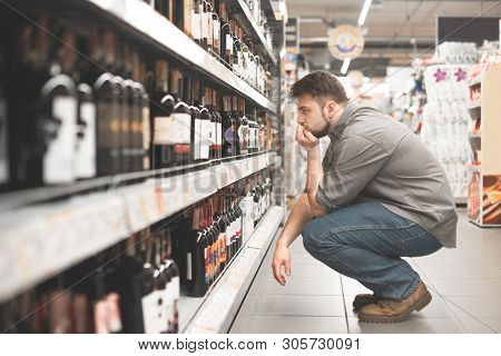 Man Sitting On The Aisle In The Supermarket And Look At The Shelves Of Wine, Buyer Chooses Wine In A