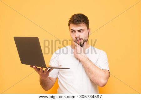 Thoughtful Man With A Beard Dressed In A White T-shirt Stands On A Yellow Background, Keeps The Lapt