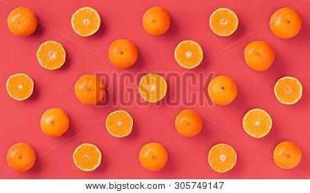 Fruit pattern of fresh orange tangerine or mandarin on living coral background. Flat lay, top view. Pop art design, creative summer concept. Citrus in minimal style.