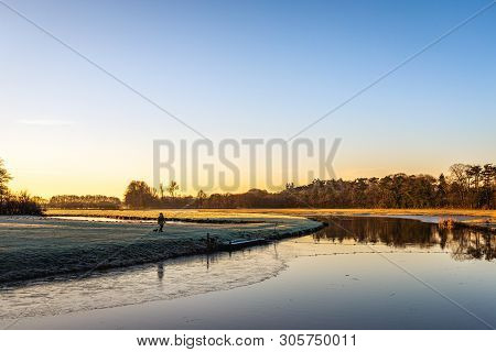 Dutch River Mark Early In The Morning On A Sunny And Windless Day In The Winter Season. An Unknown W