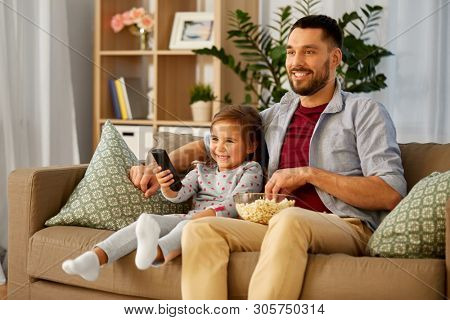 family, fatherhood and people concept - happy father and daughter with popcorn and remote control watching tv at home poster
