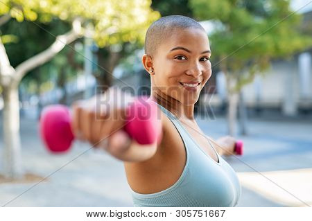 Portrait of happy bald woman exercising while looking at camera. Smiling girl doing sports outdoors with dumbbells lifting weights. Fit fitness girl in sportswear exercising outside to slim down.