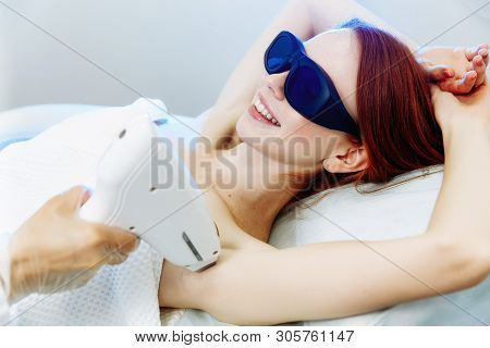 Body Care. Underarm Laser Hair Removal. Beautician Removing Hair Of Young Woman's Armpit.