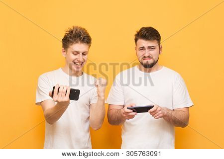 Two Young Men With Smartphones In Their Hands Play Mobile Games On A Yellow Background. Portrait Of