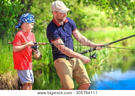 Fishermen On Riverside With Fishing Rods. Father And Son Catching Fish On Lake Shore. Family Fishing