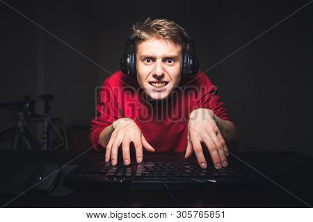 Funny Young Man Typing Text On The Computer With Two Hands And Focusing On The Computer Screen, Sitt