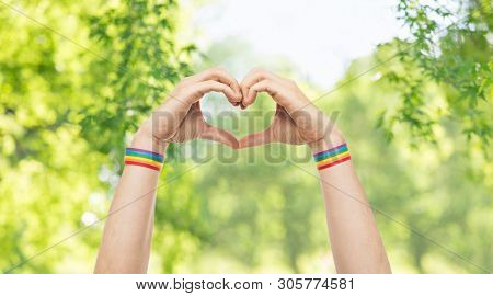 lgbt, same-sex love and homosexual relationships concept - close up of male hands with gay pride rainbow awareness wristbands showing heart gesture over green natural background