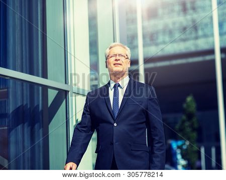 business and people concept - senior businessman walking along city street