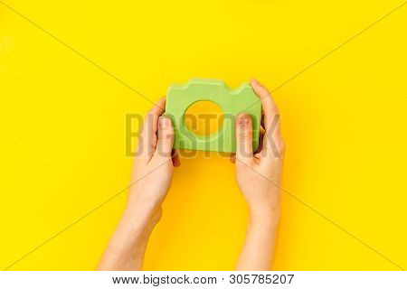 Photo Camera Concept With Hand On Yellow Background Top View