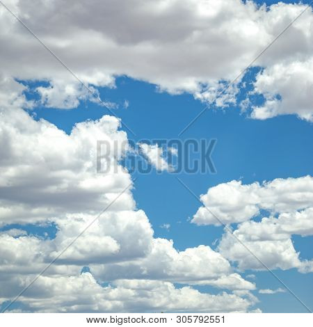 Puffy cumulus clouds on dazzling blue sky poster