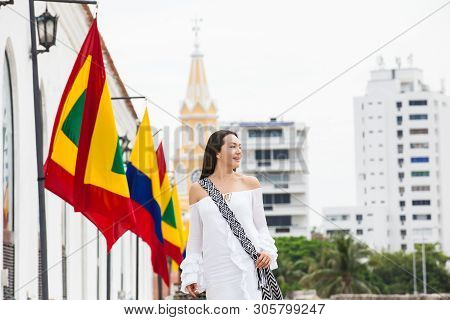 Beautiful woman walking around Cartagena de Indias next to the famous Clock Tower poster