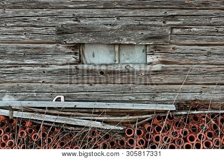 A Window In An Old Wooden Barn House At The Rural Finland. The Pipes Under The Window Are Made Of Cl
