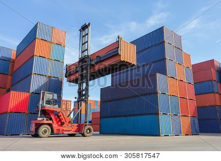 Forklift Handling Container Box Loading To Truck In Shipping Yard With Cargo Container Background, L