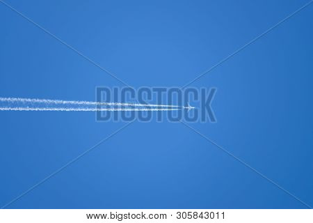 Condensation Trail From An Airplane In A Blue Sky. Flying A Passenger Plane.