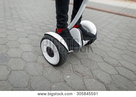 Closeup Of A Man's Feet On A Modern Hoverboard. Stylish Guy In Jeans In Sneakers Standing On A White