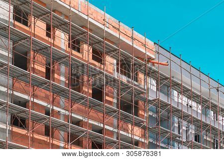 Scaffolding on empty construction site with unfinished incomplete building and blank sky as copy space poster