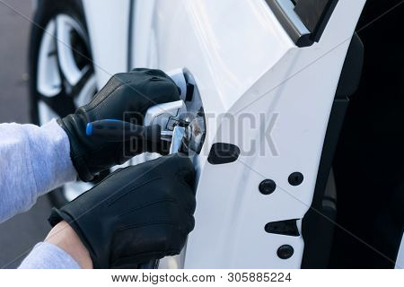 The Thief Broke The Lock On The Door Of The White Car And Opened It, Close-up