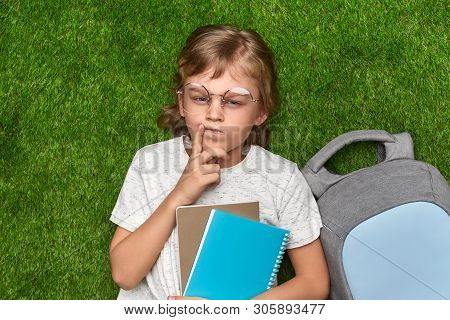 From above clever youngster with notebooks and backpack frowning and thinking while lying on green lawn before doing homework poster