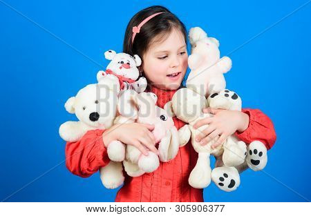 Small girl smiling face with toys. Happy childhood. Little girl play with soft toy teddy bear. Lot of toys in her hands. Childhood concept. Collecting toys hobby. Cherishing memories of childhood poster
