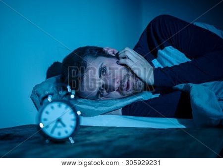 Young Man In Bed Staring At Alarm Clock Trying To Sleep Feeling Stressed And Sleepless