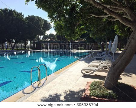 Beautiful Tropical Beach Front Hotel Resort With Swimming Pool, Sun-loungers And Palm Trees During A