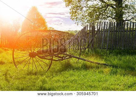 A Rusty Old Antique Hay Rake Near The Rubble Of The Fence In Summer In Russian Village