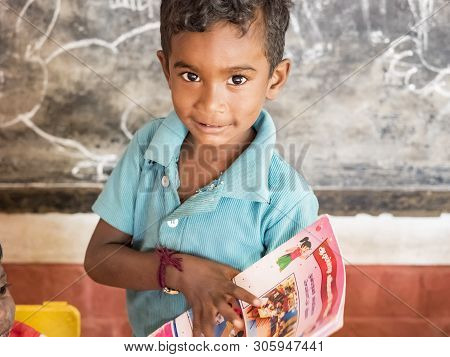 Puduchery, India - December Circa, 2018. Unidentified Cute Beautiful Poor Smiling Kid Reading A Book
