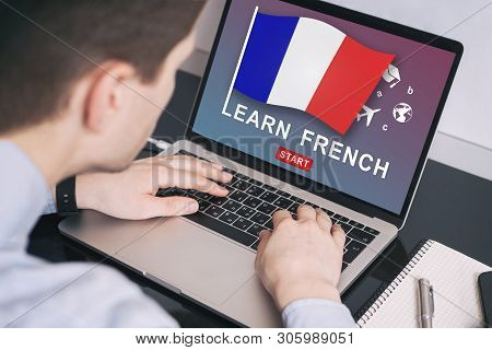 Man Working On Laptop With Learn French On A Screen. Education Learning French Language School Conce