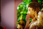 Thai people make merit, Buddhists gilding gold leaf on the face of Buddha statue to worship Buddha in Buddhist temple , people hand Gilding hand buddha selective focus Religious ceremony of Thailand. poster