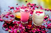Popular Ramazan drink i.e. Rose falooda or rose shake in a transparent glass along with raw milk in another glass and honey,rose syrup and rose essence also present on the surface with rose petals. poster
