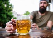 Alcohol and bar concept. Creative young brewer. Craft beer is young, urban and fashionable. Distinct beer culture. Mug cold fresh beer on table close up. Man sit cafe terrace enjoying beer defocused poster