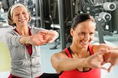 Senior woman with personal fitness trainer stretch out at gym poster