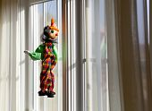 Puppet or marionette hanging in window and gazing outside into sunlit exterior poster