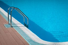 Handrail On Pool. Swimming Pool With Stair At Tropical Resort. Water Swimming Pool With Sunny Reflec