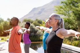 Group of senior people with closed eyes stretching arms outdoor. Mature yoga class doing breathing exercise. Women and men doing breath exercise with outstretched arms. Balance and meditation concept.