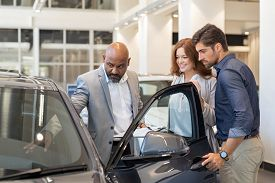 Mature african salesman showing all the car features to young couple. Car dealer showing new car to young man and beautiful woman in showroom. Couple buying a new suv in a auto dealership.