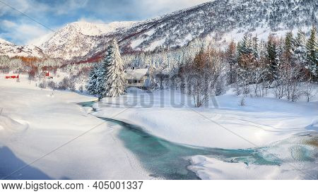 Awesome Winter Scenery With Frozen River With Wooden Houses And Snow Covered Pine Trees Near Valberg
