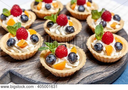 Fruit And Berry Tartlets Dessert Assorted On Wooden Tray. Closeup Of Delicious Pastry Sweets Pies Co