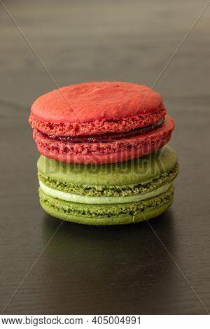 Sweet Raspberries And Pistachio Macarons Isolated On Dark Wood Background. French Pastry. Small Deli