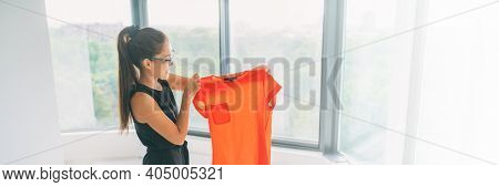 Online shopping panoramic crop. Buying new clothes concept. Asian woman happy looking at orange silk top from clothing store banner.