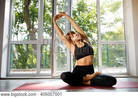 Girl Doing Warm-up While Sitting In Lotus Position. Woman Doing Yoga While Sitting On The Mat