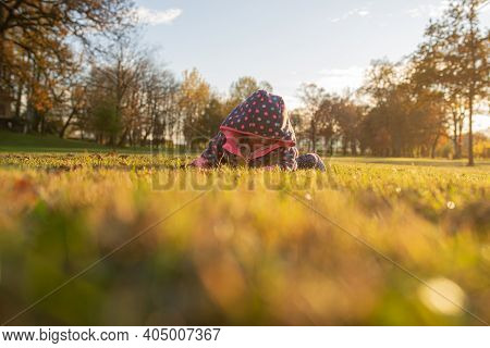 Low Angle View Of Baby Girl In Pink Sweater Lying In Autumn Grass In Beautiful Parkland.