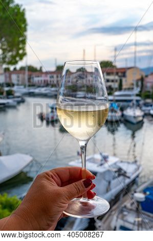 Tasting Of Local Cold White Wine In Summer With Sail Boats Haven Of Port Grimaud On Background, Prov