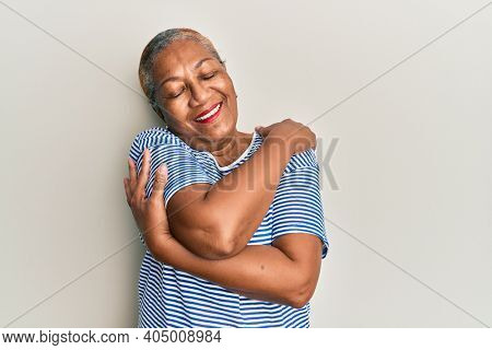 Senior african american woman wearing casual clothes hugging oneself happy and positive, smiling confident. self love and self care