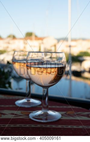 Drinking Of Local Cold Rose Wine In Summer With Sail Boats Haven Of Port Grimaud On Background, Prov