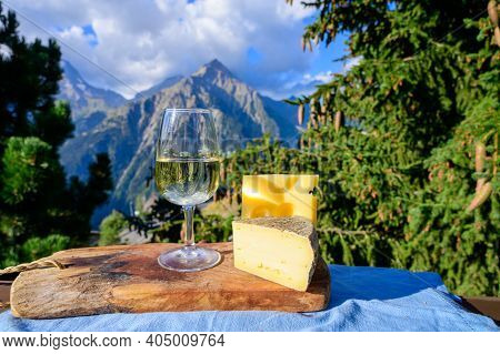 Glass Of Swiss Or Savoy Dry White Wine, Tomme And Emmental Cheese With Alpine Mountains Peaks On Bac