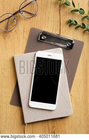 Wooden Office Desk Table With Smartphone, Paper Notebook, Clipboard, Feminine Glasses, Eucalyptus Le