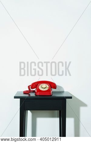 a red landline rotary dial telephone on a black wooden table, indoors, in front of a white wall with some blank space on top