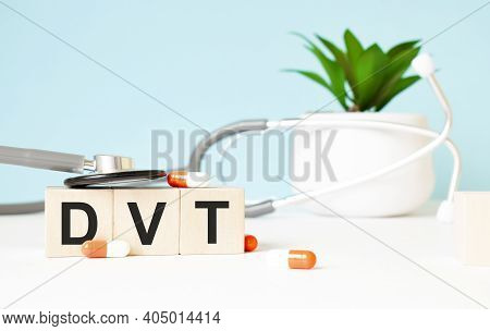 The Word Dvt Is Written On Wooden Cubes Near A Stethoscope On A Wooden Background. Medical Concept